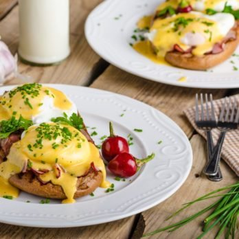 eggs benedict on a plate with cherry tomatoes