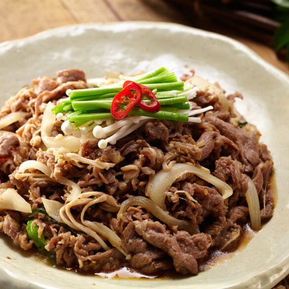 thinly sliced beef bulgogi topped with onions on white plate by cathlyn's korean kitchen